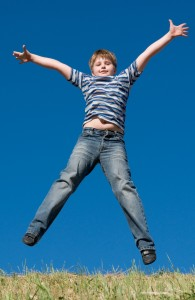 A little boy jumps with sky at background