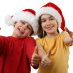 Kids wearing Santa Claus hats giving thumbs up